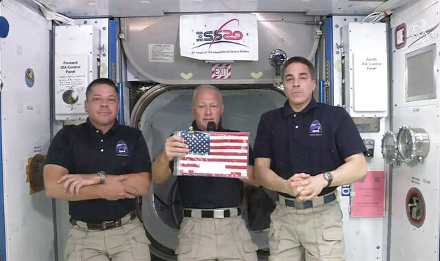 In this image taken from NASA video on Monday, June 1, 2020, NASA astronauts Robert L. Behnken, left, and Chris Cassidy right, listen as commander Douglas Hurley speaks about retrieving the American flag left behind at the International Space Station nearly a decade ago.   (NASA via AP)