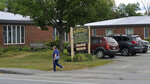 In this Aug. 19, 2020, photo, a pedestrian walks past the Maplecrest Rehabilitation and Living Center shown in Madison, Maine. State health officials said a coronavirus outbreak at the rehabilitation center, where several have died, is connected to a COVID-19 outbreak at a wedding reception in Millinocket, as an employee of the facility lives in the same household as a person who attended. (Rich Abrahamson/The Central Maine Morning Sentinel via AP)