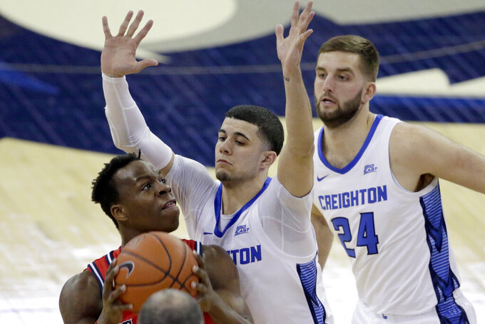 St. John's Rasheem Dunn, left, is defended by Creighton's Marcus Zegarowski, center, and Mitch Ballock (24) during the first half of an NCAA college basketball game in Omaha, Neb., Saturday, Feb. 8, 2020. (AP Photo/Nati Harnik)