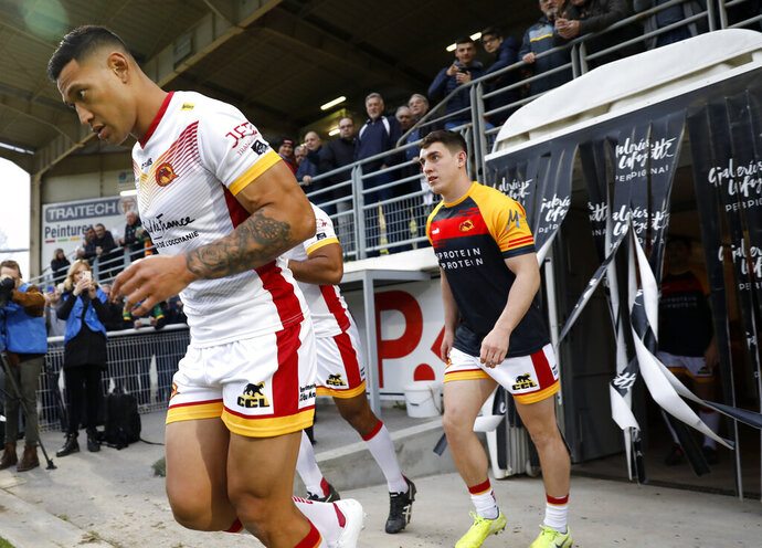 Catalans Dragons Israel Folau, left, walks out with teammates ahead of the Super League rugby match between Catalans Dragons and Castleford Tigers at Stade Gilbert Brutus in Perpignan, France, Saturday, Feb. 15, 2020. (AP Photo/Joan Monfort)