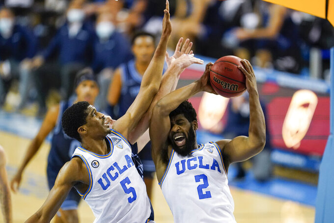 UCLA forward Cody Riley, right, grabs a rebound next to teammates Chris Smith (5) and San Diego forward Yauhen Massalski during the first half of an NCAA college basketball game Wednesday, Dec. 9, 2020, in Los Angeles. (AP Photo/Ashley Landis)