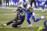 Seattle Seahawks quarterback Russell Wilson (3) slides to a stop on a carry as Los Angeles Rams outside linebacker Leonard Floyd moves in during the second half of an NFL wild-card playoff football game, Saturday, Jan. 9, 2021, in Seattle. (AP Photo/Ted S. Warren)