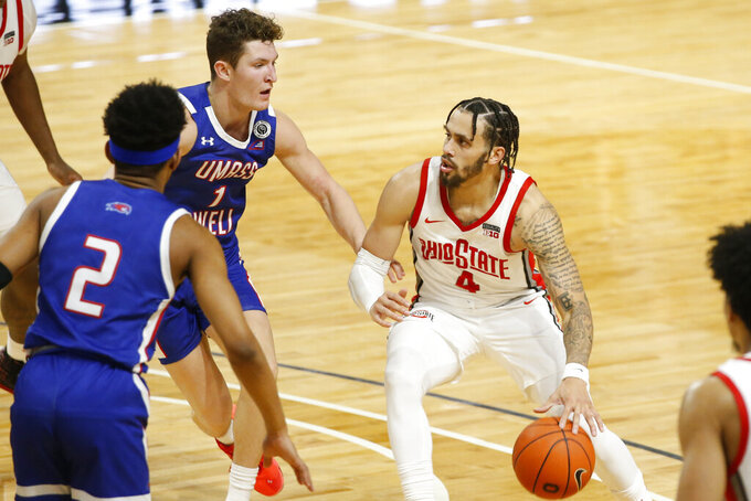 Ohio State's Duane Washington, right, drives to the basket against UMass-Lowell's Bryce Daley during the second half of an NCAA college basketball game Sunday, Nov. 29, 2020, in Columbus, Ohio. (AP Photo/Jay LaPrete)