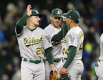 Oakland Athletics' Matt Chapman, left, Matt Olson, center, and Jesus Luzardo celebrate the 1-0 win over the Seattle Mariners in a baseball game, Saturday, Sept. 28, 2019, in Seattle. (AP Photo/John Froschauer)