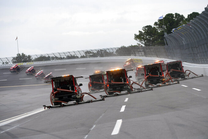 Trucks deploy to dry the track at Talladega Superspeedway before a NASCAR Cup series auto race Sunday, Oct. 3, 2021, in Talladega, Ala. (AP Photo/John Amis)