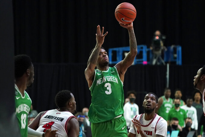 North Texas guard Javion Hamlet (3) drives to the basket between Western Kentucky guard Josh Anderson (4) and guard Taveion Hollingsworth, right, during the first half of the championship game in the NCAA Conference USA men's basketball tournament Saturday, March 13, 2021, in Frisco, Texas. (AP Photo/Tony Gutierrez)