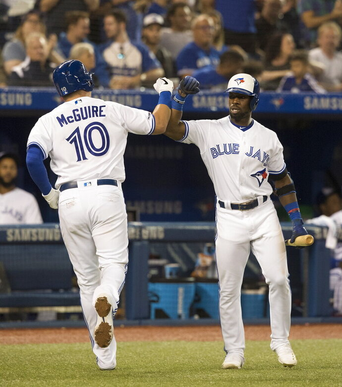 Toronto Blue Jays' Reese McGuire (10) is greeted by Jonathan Davis after McGuire hit a home run against the Boston Red Sox during the third inning of a baseball game Tuesday, Sept. 10, 2019, in Toronto. (Fred Thornhill/The Canadian Press via AP)