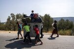 Migrants use a trash bin to move their belongings from the burned Moria refugee camp to a new army-built facility in Kara Tepe on the northeastern island of Lesbos, Greece, Friday, Sept. 18, 2020. Police on the Greek island of Lesbos on Friday resumed relocating migrants rendered homeless when fires ravaged the country's largest refugee camp amid a local COVID-19 outbreak. (AP Photo/Petros Giannakouris)