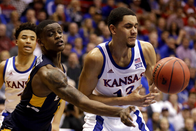 East Tennessee State guard Bo Hodges, left, knocks the ball away from Kansas guard Tristan Enaruna, right, during the second half of an NCAA college basketball game Tuesday, Nov. 19, 2019, in Lawrence, Kan. Kansas won 75-63. (AP Photo/Charlie Riedel)