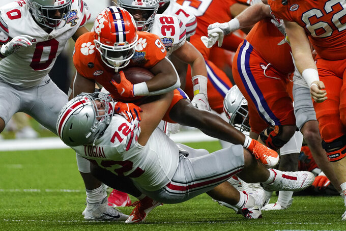 Clemson running back Travis Etienne is tackled by Ohio State defensive tackle Tommy Togiai during the first half of the Sugar Bowl NCAA college football game Friday, Jan. 1, 2021, in New Orleans. (AP Photo/John Bazemore)