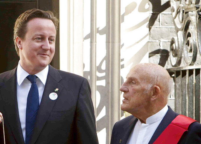 FILE - In this file photo dated Tuesday, April 12, 2011, British Prime Minister David Cameron, left, poses for photographs with British racing driver great Stirling Moss, at 10 Downing Street, in London. Stirling Moss has died at the age of 90, according to an announcement Sunday April 12, 2020, from his family. (AP Photo/Edmond Terakopian, FILE)