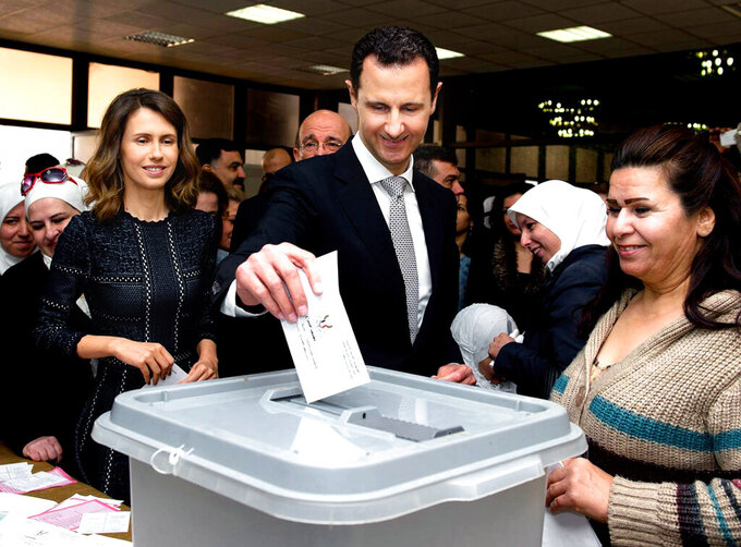FILE - This April 13, 2016 file photo released on the official Facebook page of Syrian Presidency, shows Syrian President Bashar Assad casting his ballot in the parliamentary elections, as his wife Asma, left, stands next to him, in Damascus, Syria. The office of Syrian President Bashar Assad said Monday, March 8, 2021 that Assad and his wife have tested positive for the coronavirus and are both doing well. In a statement, Assad's office said the first couple did PCR tests after they felt minor symptoms consistent with the COVID-19 illness. (Syrian Presidency via AP, File)