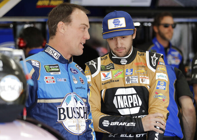Kevin Harvick, left, talks with Chase Elliott before practice for Saturday's NASCAR All-Star Cup series auto race at Charlotte Motor Speedway in Concord, N.C., Friday, May 17, 2019. (AP Photo/Chuck Burton)
