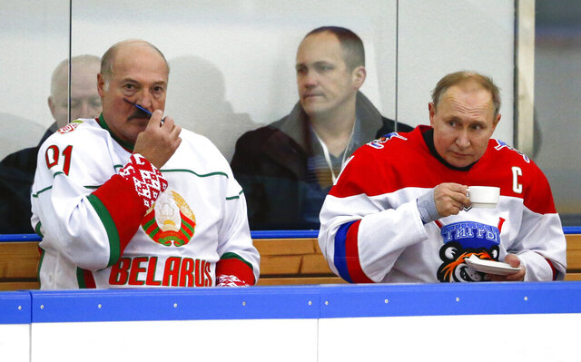 FILE - In this Friday, Feb. 7, 2020 file photo, Russian President Vladimir Putin, right, and Belarusian President Alexander Lukashenko take a break during a match of the Night Hockey League teams in Rosa Khutor in the Black Sea resort of Sochi, Russia. Lukashenko on Friday, Feb. 14 says Russia insisted on merging the two states during last week's talks on further integrating the countries' economies. He says