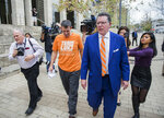 Texas men's tennis coach Michael Center, center left, walks with Defense lawyer Dan Cogdell, center right, away from the United States Federal Courthouse in Austin, Texas, Tuesday, March 12, 2019. Center is among a few people in the state charged in a scheme that involved wealthy parents bribing college coaches and others to gain admissions for their children at top schools, federal prosecutors said Tuesday. (Ricardo B. Brazziell