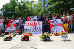 """Anti-coup protesters gather at Kamayut township in Yangon, Myanmar Thursday, April 8, 2021, with shoes willed with flowers. They walked through the markets and streets of Kamayut township with slogans to show their disaffection for military coup.  A sign, center, reads """" Kamayut Youth Strike."""" (AP Photo)"""