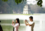 In this Feb. 21, 2019, photo, a couple take photos at the Hoan Kiem lake in Hanoi, Vietnam. The Vietnamese capital once trembled as waves of American bombers unleashed their payloads, but when Kim Jong Un arrives here for his summit with President Donald Trump he won't find rancor toward a former enemy. Instead, the North Korean leader will get a glimpse at the potential rewards of reconciliation. (AP Photo/Hau Dinh)