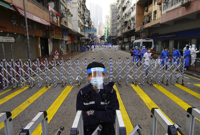A police officer stands guard at the Yau Ma Tei area, in Hong Kong, Saturday, Jan. 23, 2021. Thousands of Hong Kong residents were locked down Saturday in an unprecedented move to contain a worsening outbreak in the city, authorities said. (AP Photo/Vincent Yu)