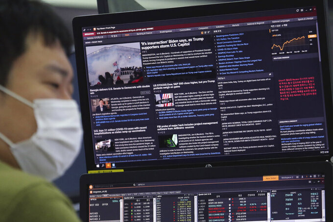 A currency trader works in front of a screen which shows a report on a mob by U.S. President Donald Trump supporters, at the foreign exchange dealing room of the KEB Hana Bank headquarters in Seoul, South Korea, Thursday, Jan. 7, 2021. (AP Photo/Ahn Young-joon)