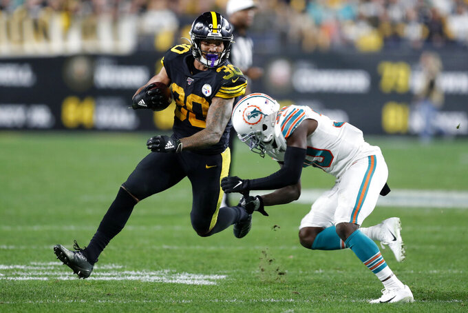 Pittsburgh Steelers running back James Conner (30) runs around Miami Dolphins defensive back Chris Lammons (30) during the second half of an NFL football game in Pittsburgh, Monday, Oct. 28, 2019. (AP Photo/Keith Srakocic)