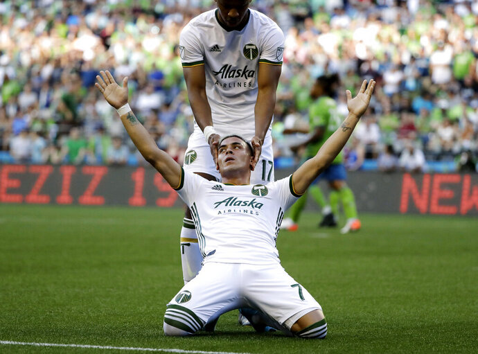 Portland Timbers forward Brian Fernandez, front, celebrates with Jeremy Ebobisse, top, after Fernandez scored a goal against the Seattle Sounders during the first half of an MLS soccer match, Sunday, July 21, 2019, in Seattle. (AP Photo/Ted S. Warren)