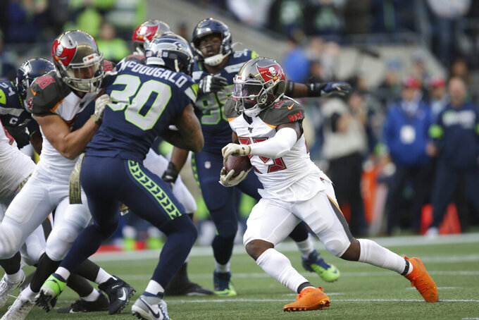 Tampa Bay Buccaneers running back Peyton Barber, right, rushes against the Seattle Seahawks during the first half of an NFL football game, Sunday, Nov. 3, 2019, in Seattle. (AP Photo/Scott Eklund)