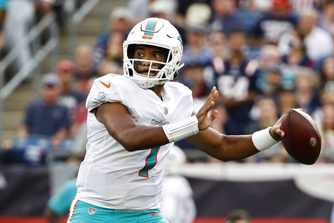 FILE - In this Sunday, Sept. 12, 2021 file photo, Miami Dolphins quarterback Tua Tagovailoa passes against the New England Patriots during the first half of an NFL football game in Foxborough, Mass. Quarterback Tua Tagovailoa has fractured ribs and won't play Sunday, Sept. 26, 2021 when the Dolphins visit the Raiders. Miami coach Brian Flores did not want to offer a timetable for a potential return but said Tagovailoa is already improving. Jacoby Brissett will start against Las Vegas.(AP Photo/Winslow Townson, File)