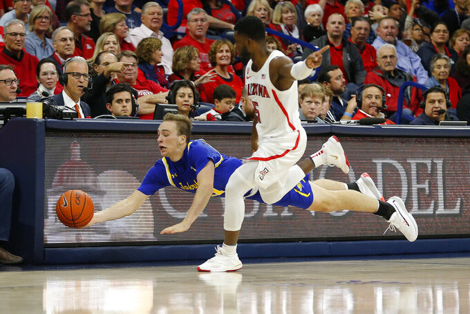 South Dakota State guard Noah Freidel, left, saves the ball in front of Arizona guard Max Hazzard (5) in the second half during an NCAA college basketball game, Thursday, Nov. 21, 2019, in Tucson, Ariz. (AP Photo/Rick Scuteri)