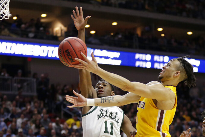 Minnesota's Amir Coffey, right, goes to the basket against Michigan State's Aaron Henry (11) during the first half of a second round men's college basketball game in the NCAA Tournament, in Des Moines, Iowa, Saturday, March 23, 2019. (AP Photo/Nati Harnik)