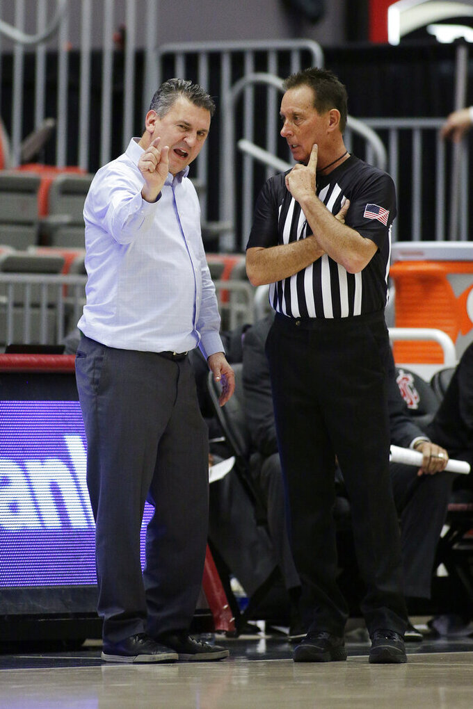Washington State head coach Kyle Smith, left, speaks with an official during the second half of an NCAA college basketball game against Arizona State in Pullman, Wash., Wednesday, Jan. 29, 2020. Washington State won 67-65. (AP Photo/Young Kwak)