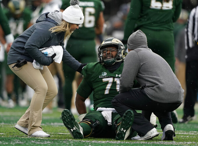 Colorado State offensive lineman Jeff Taylor is tended by trainers during the first half of an NCAA football game against Utah State, Saturday, Nov. 17, 2018, in Fort Collins, Colo. (AP Photo/Jack Dempsey)