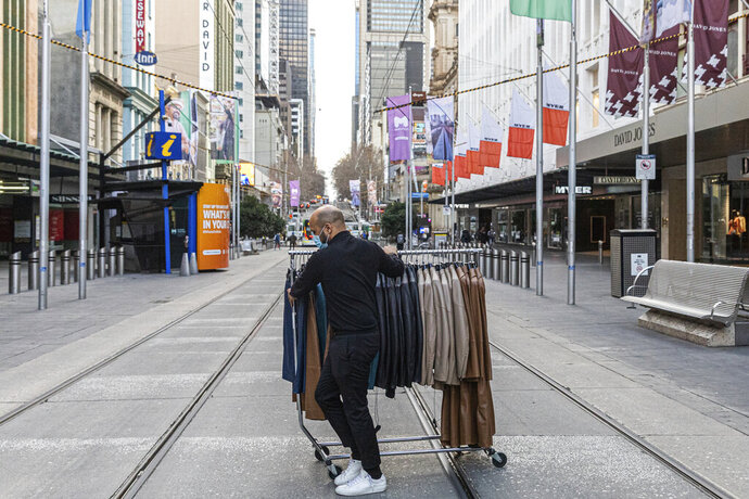A department store employee wheels clothes across the Bourke Street Mall as retail businesses prepare to close their doors to walk-in customers as lockdown of Melbourne forces people to stay at home if not working due to the continuing spread of the coronavirus, Wednesday, Aug. 5, 2020. Victoria state, Australia's coronavirus hot spot, announced on Monday that businesses will be closed and scaled down in a bid to curb the spread of the virus. (AP Photo/Asanka Brendon Ratnayake)