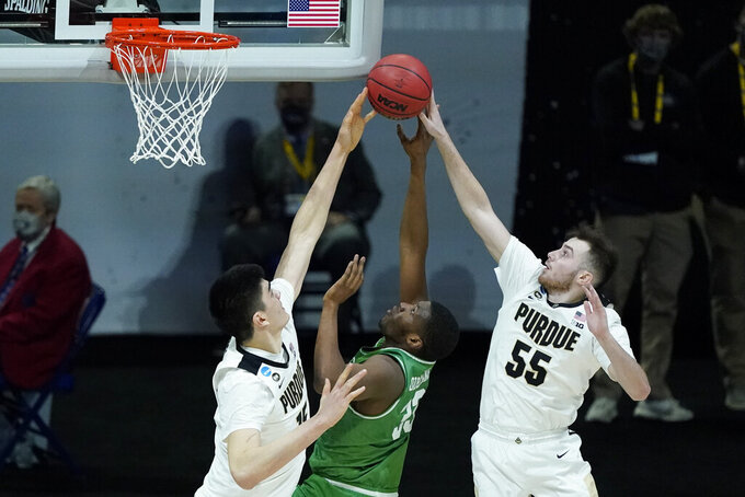 North Texas's Abou Ousmane (33) has his shot blocked by Purdue's Zach Edey (15) and Sasha Stefanovic (55 during the first half of a first-round game in the NCAA men's college basketball tournament at Lucas Oil Stadium, Friday, March 19, 2021, in Indianapolis. (AP Photo/Darron Cummings)