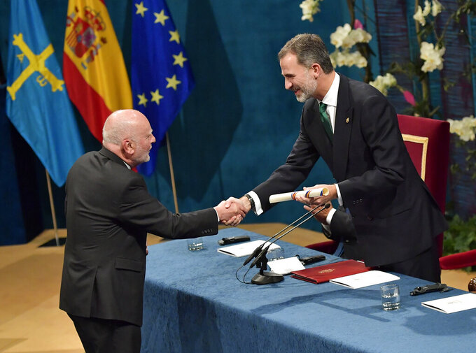 FILE - In this Friday Oct. 20, 2017 file photo, writer and poet Adam Zagajewski from Poland, left, receives the Princess of Asturias award for Literature, presented by Spanish King Felipe VI, during the Princess of Asturias awards ceremony, in Oviedo, northern Spain. One of Poland's greatest poets, Adam Zagajewski, who wrote a poem that came to symbolize the world's sense of shock and loss after the Sept. 11, 2001, attacks in the United States, died in Krakow on Sunday March 21, 2021, aged 75. (AP Photo/Alvaro Barrientos, File)