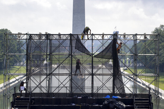 FILE - In this July 5, 2019, file photo workers dismantle a riser, with the Washington Monument and Lincoln Memorial Reflecting Pool behind, as clean up is underway after Fourth of July celebrations in Washington. On Wednesday, July 17, the Federal Reserve releases its latest