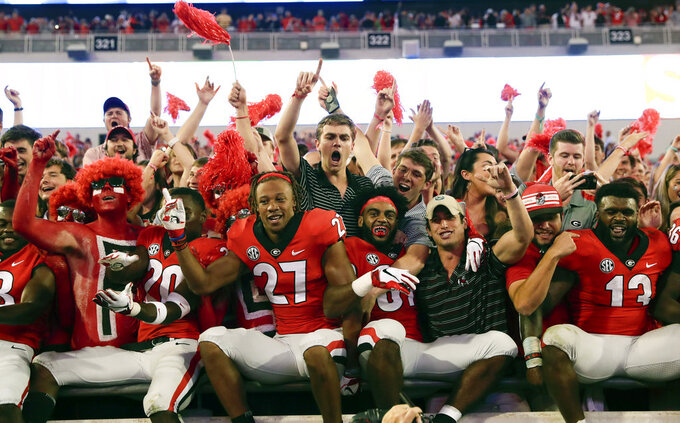 Georgia players celebrate with fans after defeating Florida in an NCAA college football game Saturday, Oct. 27, 2018, in Jacksonville, Fla. Georgia won, 36-17. (AP Photo/John Raoux)