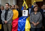 Opposition leader Henrique Capriles, left, and lawmaker Dinorah Figuera, stand vigil around the flag-draped casket containing the remains of opposition activist Fernando Alban, during a solemn ceremony at the National Assembly headquarters, in Caracas, Venezuela, Tuesday, Oct. 9, 2018. International condemnation of Venezuela's leadership poured in Tuesday following the suspicious death of Alban authorities say evaded justice by throwing himself from the 10th floor of a police building. (AP Photo/Ariana Cubillos)