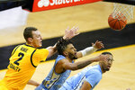 North Carolina guard R.J. Davis, center, is fouled by Iowa forward Jack Nunge, left, during the second half of an NCAA college basketball game, Tuesday, Dec. 8, 2020, in Iowa City, Iowa. Iowa won 93-80. (AP Photo/Charlie Neibergall)
