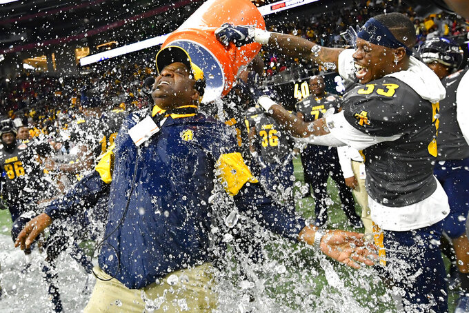 FILE - In this Dec. 21, 2019, file photo, North Carolina A&T coach Sam Washington is doused by defensive back Jalon Bethea during the final seconds of the Celebration Bowl NCAA college football game against Alcorn State, in Atlanta. Teams in the SWAC as well as many other HBCUs across the country play in the Football Championship Subdivision (FCS). Schools at this level earn some money from television contracts, but nothing like the multimillion-dollar deals for the Power Five.  In the SWAC, the main source of revenue from football comes from putting fans in the stands and there are no substitutes for that at schools that often have limited resources. (John Amis/Atlanta Journal-Constitution via AP, File)