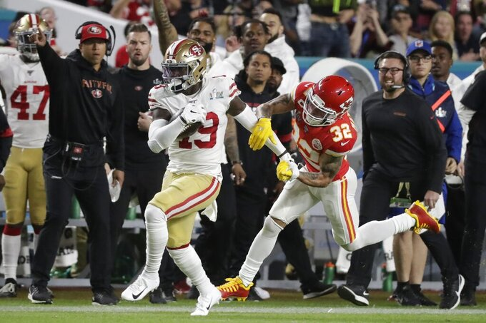 San Francisco 49ers' Deebo Samuel (19) runs in front of Kansas City Chiefs' Tyrann Mathieu (32) during the first half of the NFL Super Bowl 54 football game Sunday, Feb. 2, 2020, in Miami Gardens, Fla. (AP Photo/Wilfredo Lee)
