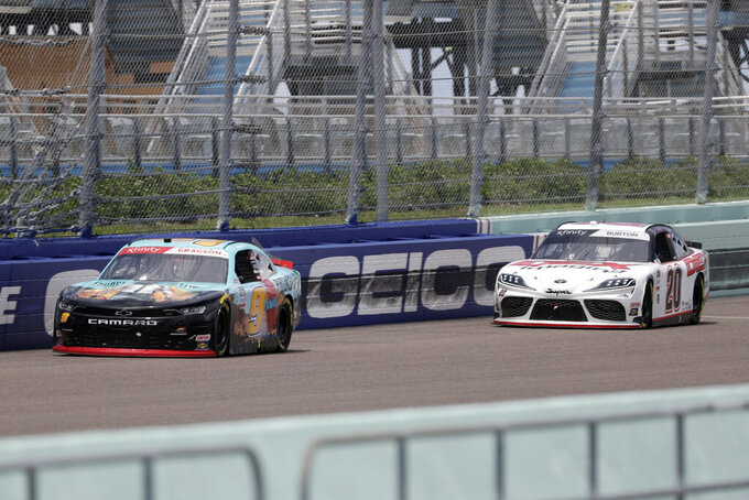 Noah Gragson (9) and Harrison Burton (20) battle during a NASCAR Xfinity Series auto race Sunday, June 14, 2020, in Homestead, Fla. (AP Photo/Wilfredo Lee)