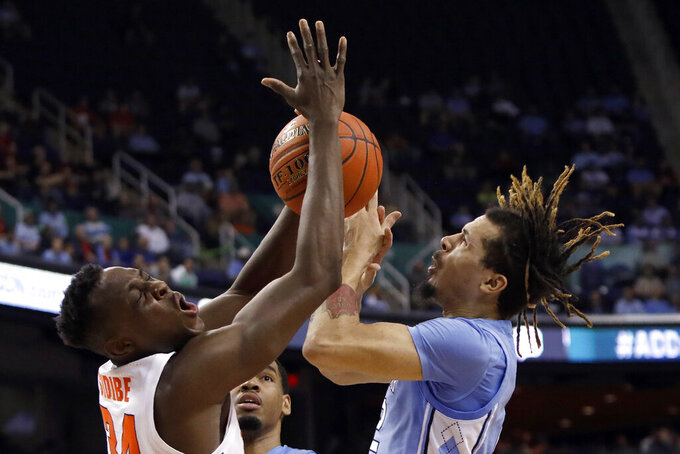 Syracuse forward Bourama Sidibe, left, and North Carolina guard Cole Anthony reach for the ball during the first half of an NCAA college basketball game at the Atlantic Coast Conference tournament in Greensboro, N.C., Wednesday, March 11, 2020. (AP Photo/Ben McKeown)