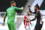 Newcastle's goalkeeper Martin Dubravka and teammate Valentino Lazaro elbow bump at the end of the English Premier League soccer match between Newcastle United and Sheffield United at St James' Park stadium in NewCastle, England, Sunday, June 21, 2020. (Owen Humphreys/Pool via AP)