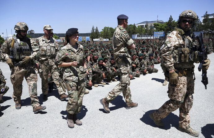 FILE- In this Monday, May 27, 2019 file photo, NATO forces attend the graduation ceremony of Afghan National Army soldiers from a 3-month training program at the Afghan Military Academy in Kabul, Afghanistan. (AP Photo/Rahmat Gul, File)