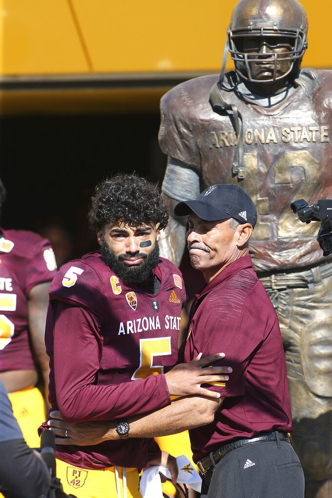 An emotional Arizona State quarterback Manny Wilkins (5) embraces head coach Herm Edwards as he is introduced for his final game at Sun Devil Stadium prior to an NCAA college football game against UCLA, Saturday, Nov. 10, 2018, in Tempe, Ariz. (AP Photo/Ralph Freso)