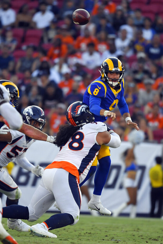Los Angeles Rams quarterback Brandon Allen, top, throws under pressure from Denver Broncos nose tackle Mike Purcell during the first half of an NFL preseason football game Saturday, Aug. 24, 2019, in Los Angeles. (AP Photo/Mark J. Terrill)