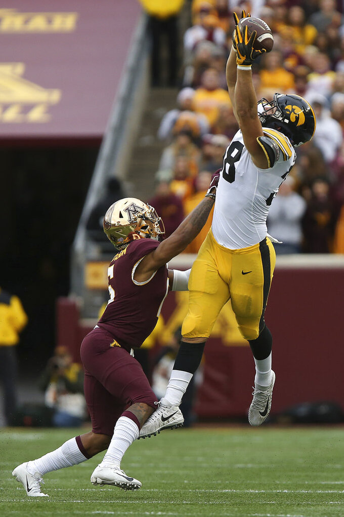 Iowa tight end T.J. Hockenson tries to catch the ball against Minnesota's defensive back Chris Williamson during an NCAA college football game Saturday, Oct. 6, 2018, in Minneapolis. Iowa won 48-31. (AP Photo/Stacy Bengs)