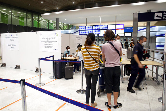 People register prior to be tested with the COVID-19 test, at the Roissy Charles de Gaulle airport, outside Paris, Saturday, Aug. 1, 2020. Travelers entering France from 16 countries where the coronavirus is circulating widely are having to undergo virus tests upon arrival at French airports and ports.(AP Photo/Thibault Camus)