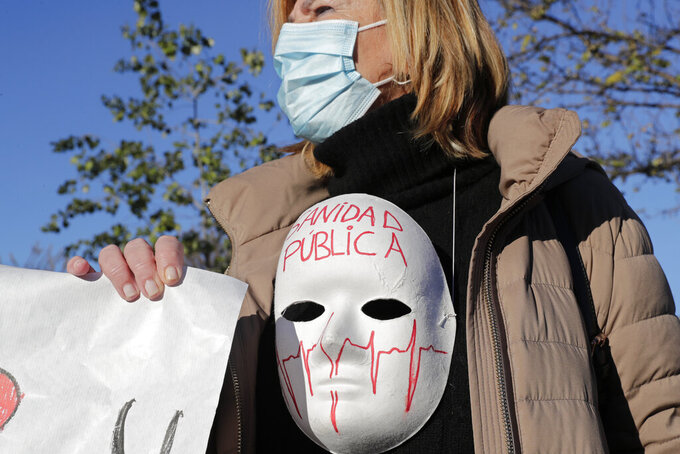 One of around 200 health professionals protest at the entrance of the Nurse Isabel Zendal Hospital as officials entered the state-of-the-art facility, built in 100 days at a cost of 100 million euros (119 dolllars), twice the original budget in Madrid, Spain, Tuesday, Dec. 1, 2020. Authorities in Madrid held a ceremony to open part of a 1,000-bed hospital for emergencies that critics say is no more than a vanity project, a building with beds not ready to receive patients and unnecessary now that contagion and hospitalizations are waning. Spain has officially logged 1.6 million infections and over 45,000 deaths confirmed for COVID-19 since the beginning of the year. Message on mask reads ' Public heath service'. (AP Photo/Paul White)