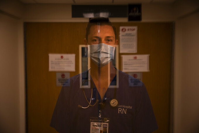 """In this photo created with an in-camera multiple exposure, registered nurse Anthony Wilkinson, part of a group of nurses who had been treating coronavirus patients in an intensive care unit, stands for a photo in the empty COVID-19 ICU at Providence Mission Hospital in Mission Viejo, Calif., Tuesday, April 6, 2021. Wilkinson still thinks about those 30 hours — the ones when three patients died. """"You try to keep somebody alive, but their body is decomposing,"""" says Wilkinson. (AP Photo/Jae C. Hong)"""